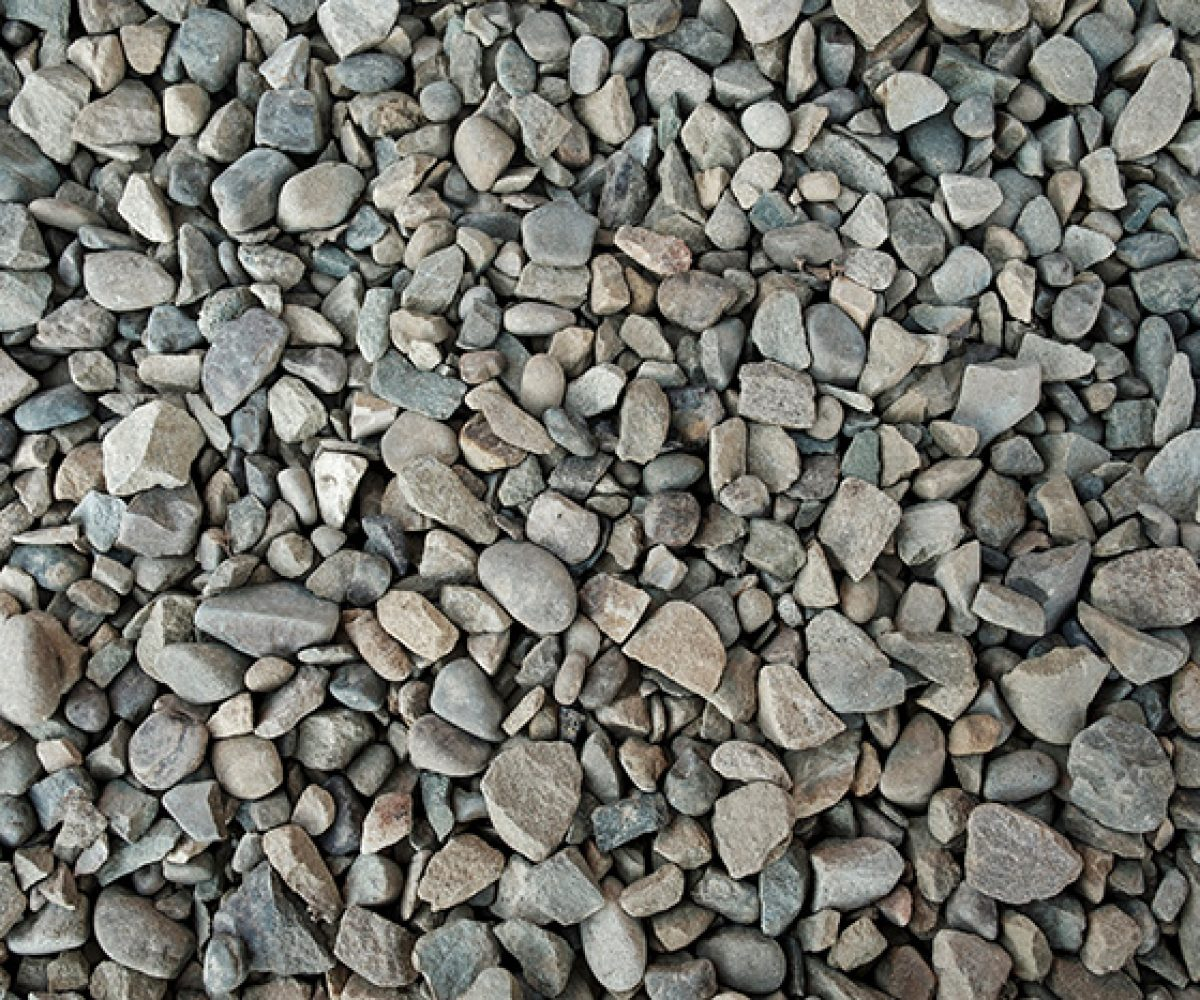 Background texture of grey gravel with irregular stones and pebbles viewed from above in a full frame view